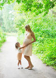 Pregnant woman, mother and little daughter child walking together in summer Stock Photography