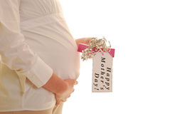 Pregnant woman with mothers day present. Pregnant woman profile holding Mother's Day present with tag royalty free stock image