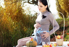 Pregnant woman on the nature, autumn time. Pregnant pretty happy woman is reasting near autumn lake with apples and pumpkin. Love and care concept royalty free stock images