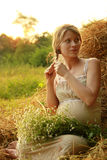 Pregnant woman on nature near the haystacks Royalty Free Stock Image