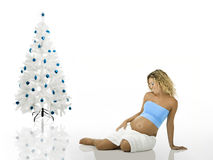 Pregnant woman near a Christmas Tree Stock Photo