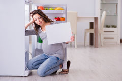 The pregnant woman near fridge with blank message Royalty Free Stock Images