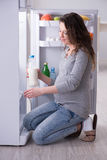 The pregnant woman near fridge looking for food and snacks Royalty Free Stock Images