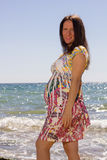 Pregnant woman near the sea and smile Stock Image