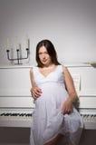 Pregnant woman near white piano Royalty Free Stock Photos