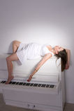 Pregnant woman near white piano Stock Images