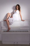Pregnant woman near white piano Stock Photo