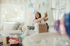 Pregnant woman with new gift at baby shower. Smiling young pregnant woman receiving gifts from her friends. Female opening presents received at baby shower party royalty free stock photos