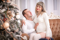 Pregnant woman New Year gifts. Young beautiful couple posing near the Christmas tree Stock Photography