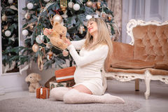Pregnant woman New Year gifts. Young beautiful couple posing near the Christmas tree Royalty Free Stock Photo