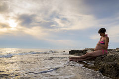 Pregnant woman in ninth month of pregnancy sitting on a rock by Royalty Free Stock Images