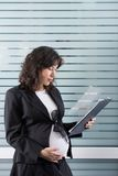 Pregnant woman in the office stock photography