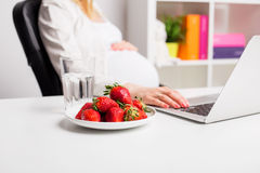 Pregnant woman in office working and having strawberries Stock Photo