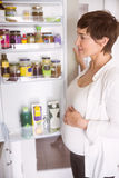 Pregnant woman opening the fridge Stock Photos