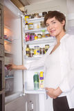 Pregnant woman opening the fridge Stock Photo