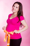 Pregnant woman with orange ribbon on her belly. Studio portrait of pregnant smiling woman with orange ribbon on her belly on pink background royalty free stock photos