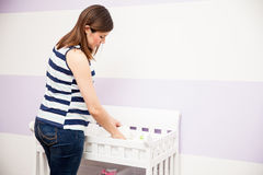 Pregnant woman organizing the nursery. Attractive young pregnant woman storing diapers and organizing her diaper changing station in a nursery at home Stock Photos