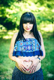Pregnant woman outdoor with heart shaped hands Stock Photos