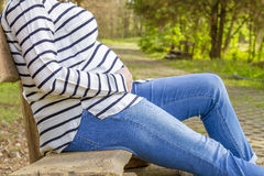 Pregnant woman outdoor in the park on bench Stock Images