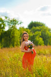 Pregnant woman outdoors with flowers Stock Photo