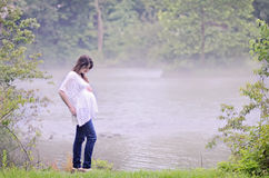 Pregnant woman peaceful. Pregnant woman outdoors by a foggy river on a peaceful morning Stock Image