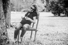 Pregnant woman outdoors. Sitting on a chair, monochrome royalty free stock images