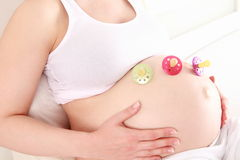 Pregnant woman with pacifiers on her baby belly Stock Images