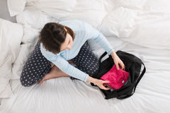 Pregnant Woman Packing Baby Clothes Into Bag Royalty Free Stock Photos