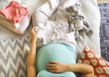 Pregnant woman is packing baby clothes. For going to maternity hospital top view stock photography