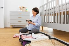 Pregnant woman packing bag for maternity hospital. Pregnancy, nursery and people concept - happy pregnant middle-aged woman packing bag or suitcase for maternity stock photography