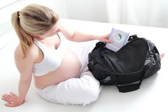 Pregnant woman packing hospital bag royalty free stock photography