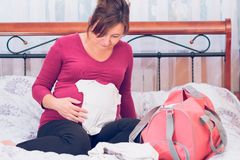 Pregnant woman packing hospital bag Royalty Free Stock Photos