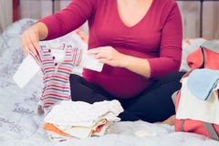 Pregnant woman packing hospital bag Stock Image