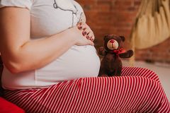 Pregnant woman in pajamas holding a teddy bear on the bed in the bedroom stock photo
