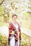 Pregnant woman in park among blooming trees in spring royalty free stock photos