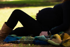 Pregnant woman at park in warm weather Royalty Free Stock Photos