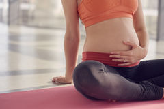 Pregnant woman part with space. Young pregnant woman sitting on floor, part of body royalty free stock photography