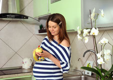 Pregnant woman peel the apple. Young pregnant woman peel the apple, healthy food Royalty Free Stock Images