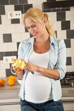 Pregnant woman peeling an apple. Attractive pregnant woman standing in the kitchen peeling an apple Royalty Free Stock Photography