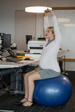 Pregnant woman performing stretching exercise on fitness ball Royalty Free Stock Photo