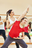 Pregnant woman with personal trainer doing fitness exercise. Female fitness personal instructor training pregnant women by doing exercise in sport club Stock Images
