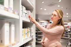 Pregnant woman at pharmacy or cosmetics store. Pregnancy, people, healthcare, beauty and bodycare concept - pregnant woman choosing medicine at pharmacy or Royalty Free Stock Photo