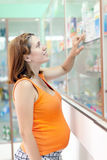 Pregnant woman  at  pharmacy drugstore Royalty Free Stock Image
