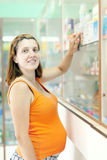 Pregnant woman at the pharmacy drugstore. Pregnant woman chooses drugs at the pharmacy drugstore royalty free stock photo
