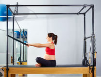 Pregnant woman pilates reformer forward push Stock Images
