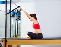 Pregnant woman pilates reformer forward push. Through exercise workout at gym Stock Photo
