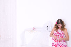 Pregnant woman in pink dress in room Royalty Free Stock Photos