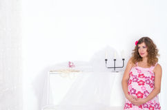 Pregnant woman in pink dress in room Royalty Free Stock Image