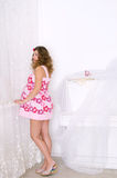 Pregnant woman in pink dress in room Royalty Free Stock Photo