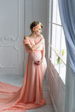 Pregnant woman in pink evening dress standing near the window. Fashion shot. Royalty Free Stock Images